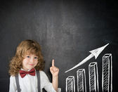 Happy child against blackboard with bar graph — Stock Photo