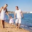 Happy family playing at the beach — Stok fotoğraf #9716339