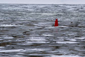 Deep Stream. Red navigation buoy in the river covered with white and grey colored ice — Stock Photo