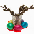 Swelling buds in a glass and Easter eggs, isolated - Stock Photo