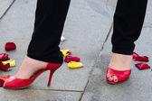 Pernas femininas entre pétalas de rosa — Fotografia Stock