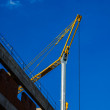 Small crane and wall against the blue sky — Stock Photo #25126359