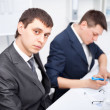 Stock Photo: Two young businessmen working together in office