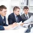 Stock Photo: Team of young business men doing some paperwork together at offi