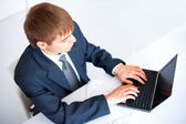 Top view of young businessman working on laptop in office — Stock Photo