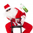 Santa Claus sitting in a chair wearing sunglasses holds a bottle — Stock Photo