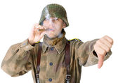 Soldier smoking a cigar and gives a thumb down — Stock Photo