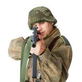 Soldier shoots submachine gun isolated on white — Stock Photo