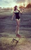 Hermosa chica equilibrios en la parte trasera de la silla al aire libre. — Foto de Stock