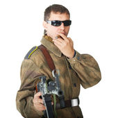 Soldier wearing sunglasses with machine gun smoking a cigar — Stock Photo