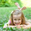 Beautiful little girl is lying on the green grass — Stock Photo