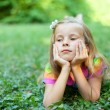 Beautiful little girl is lying on the green grass — Stock Photo #22174107