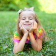 Stock Photo: Beautiful little girl is lying on the green grass