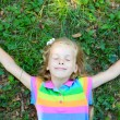Little girl with closed eye lying on grass — Stock Photo #22174131