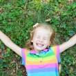 Stock Photo: Little funny girl with closed eye lying on grass