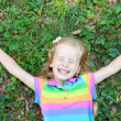 Little funny girl with closed eye lying on grass — Stock Photo #22174167