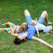 Joyful family enjoying themselves laying on the grass in park - Stock Photo