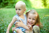 Sister and brother lying on green grass — Stock Photo