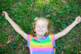 Little girl with closed eye lying on grass — Stock Photo