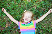 Little funny girl with closed eye lying on grass — Stock Photo