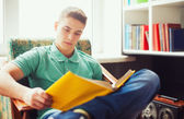 Student sitting on chair and reading book — Stock Photo