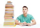 Young frustrated student sitting at the desk with high books sta — Stock Photo