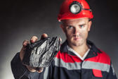 Coal miner showing lump of coal — Stock Photo