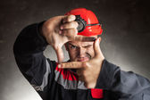 Coal miner looking through a finger frame — Stock Photo