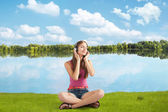 Beautiful girl in headphones listens to music near river — Stock Photo