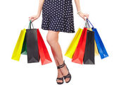 Waist-down view of woman with shopping bags — Stock Photo