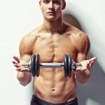 Young bodybuilder man offering dumbbell — Stock fotografie