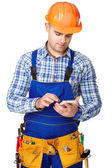 Young construction worker with smartphone — Stock Photo