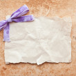 Ripped piece of paper with purple bow on grunge paper background — Stock Photo #6479416