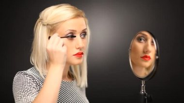Beautiful blonde model putting on mascara in the mirror — Stock Video