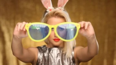 Blonde girl with bunny ears putting on oversized glasses — Stock Video