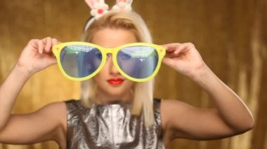 Blonde model with bunny ears putting on oversized glasses — Stock Video