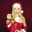 Sexy Christmas girl with tree ornaments on red background — Stock Photo