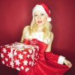 Attractive Christmas girl with present on red background — Stock Photo