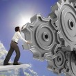 Business man pushing a cogwheel to make it work — Stockfoto