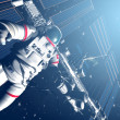 The astronaut and flying modern satellite in outer space — Stock Photo