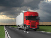 Red truck on blurry asphalt road over blue cloudy sky background — Stock Photo