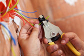 Electrician peeling off wires — Stock Photo
