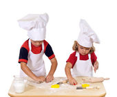 Children making cookies dressed as chefs — Stock Photo