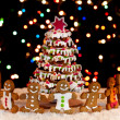 Happy gingerbread around the christmas tree - Stock Photo
