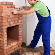 Worker building brick stove or fireplace — Stock Photo