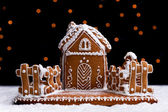 Gingerbread cookie house on dark background — Stock Photo