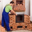 Worker mounting door to a masonry heater — Stock Photo
