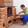Stock Photo: Worker building masonry heater
