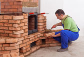Worker building masonry heater — Photo