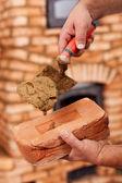 Building a masonry heater - closeup on worker hands — 图库照片